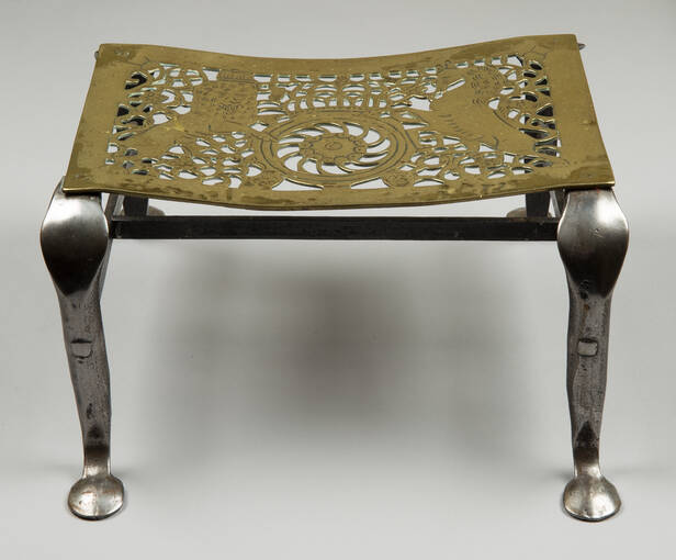 A metal trivet with ornate legs and brass-type top, featuring a unicorn design.
