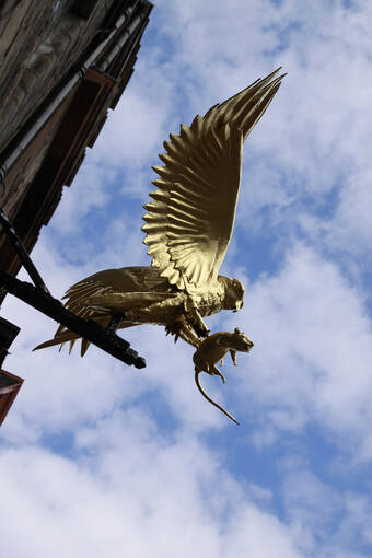 Golden bird statue hangs at the front of Gladstone's Land