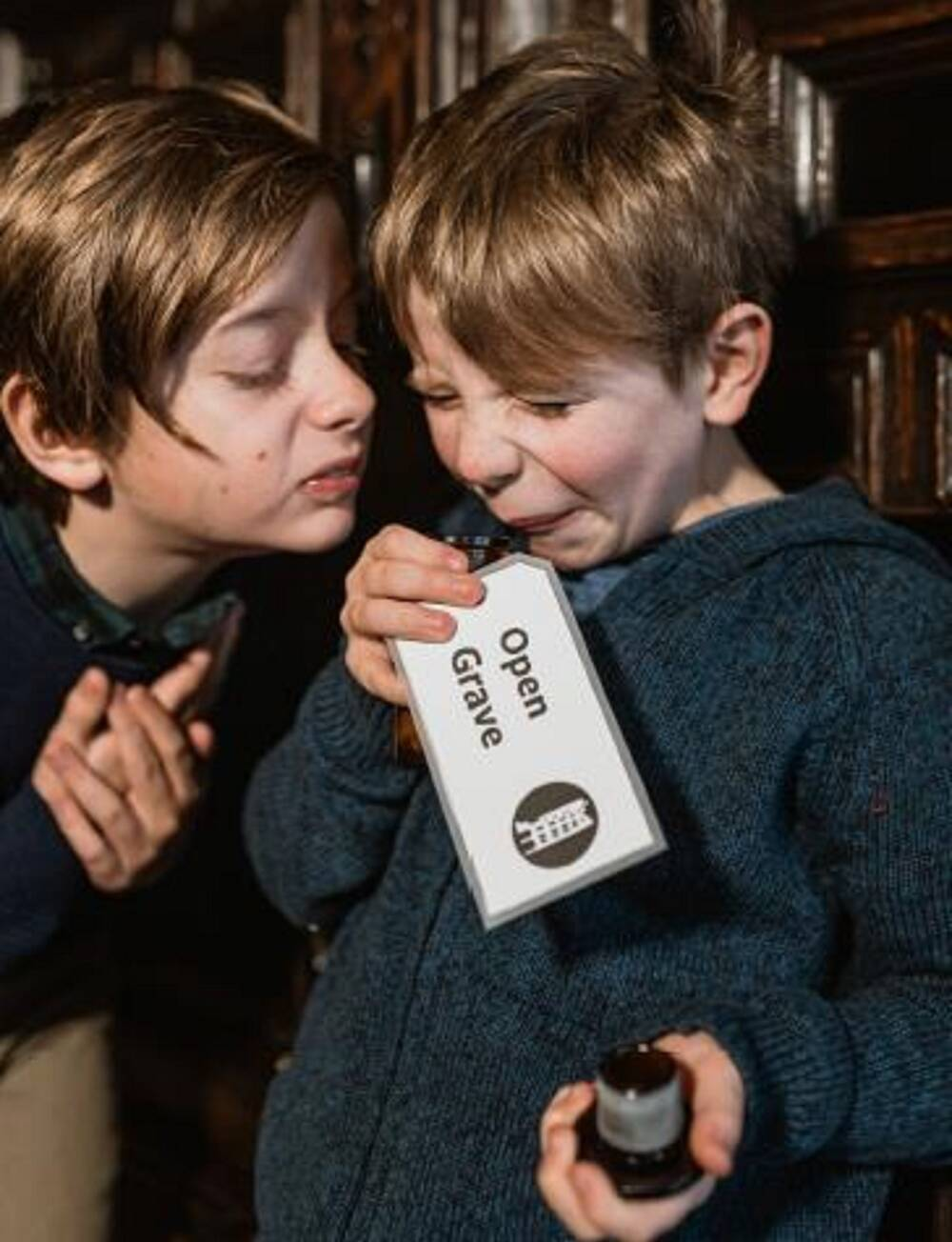Two young boys grimace as they smell an open small bottle. The label of the bottle reads: Open Grave. One boy holds the stopper out in front of him.