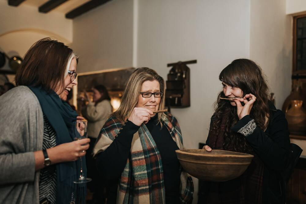 Three women hold a large wooden bowl. Two of them are smelling scented sticks from it. One is smiling, the other is grimacing!
