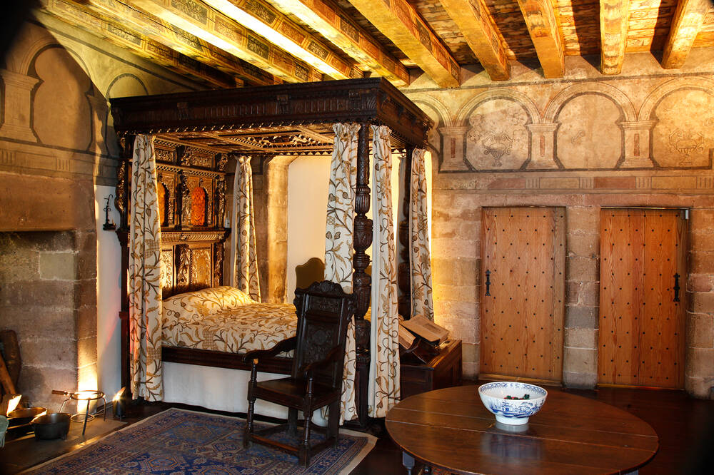 A bedroom re-created in the 17th-century style. The room has beautiful wooden painted ceilings and panelled walls. A four poster bed with floral curtains stands in the corner.