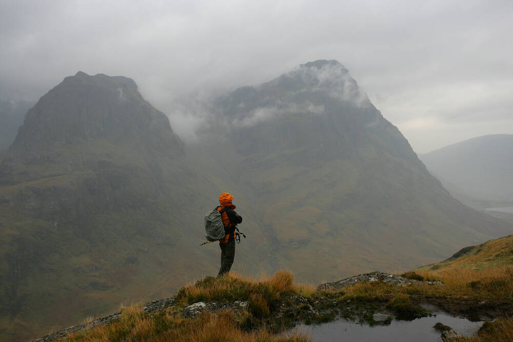 A walker looking out across the landscape of the highlands.