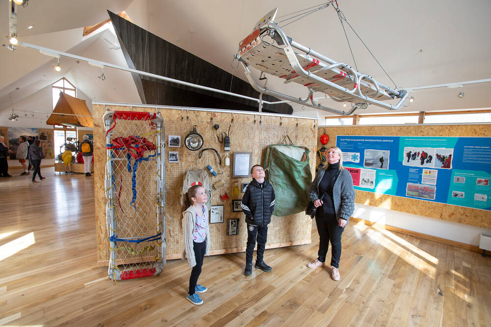 A mother and two children look up at a rescue sledge suspended from the ceiling in the new Glencoe Visitor Centre. It is an airy space with polished wooden floors and spaced out exhibits and panels.