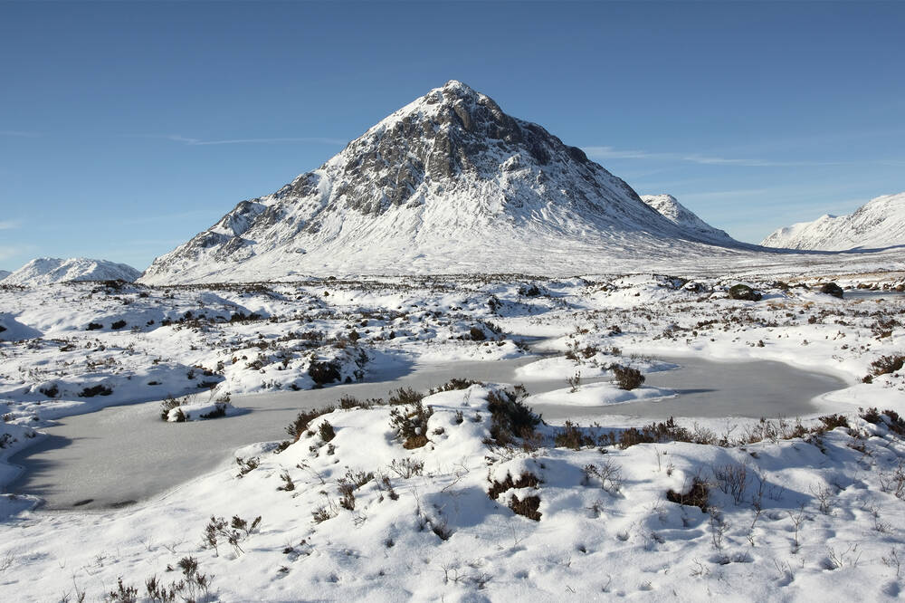 Glencoe in winter. Buachaille Etive Beag, covered in snow, dominates the image with snow-covered moorland and frozen lochans to the foreground. The sky is a deep blue.