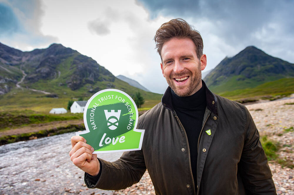 Craig McGinlay holding a National Trust for Scotland sign