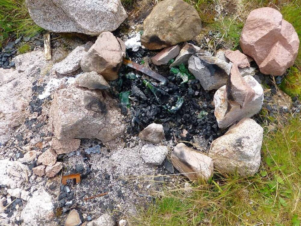 The remains of a campfire, surrounded by a stone circle, showing scorched ground and hazardous waste left behind