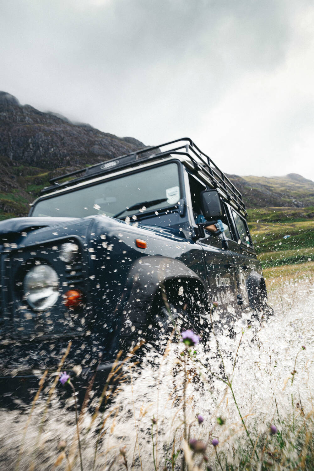 A Land Rover splashing through a burn in Glencoe