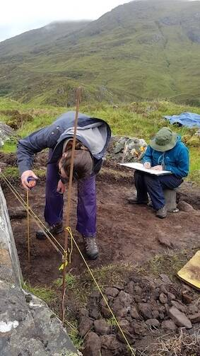 Two people at work in an excavation trench at Glenshiel. One sits at the edge, recording data; the other stands by the taped fence, measuring the height from the ground.