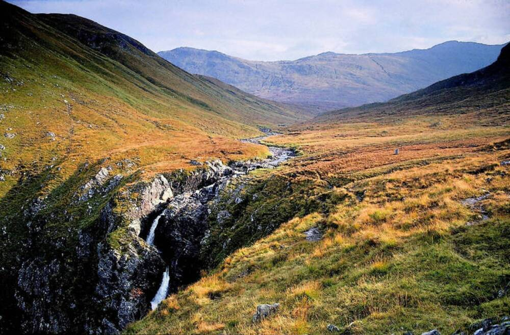 The top of a waterfall, surrounded by a moorland mountain plateau, with mountains in the distance.