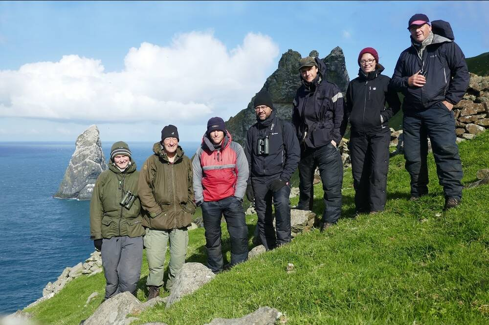 A group photo of the team responsible for carrying out the seabird survey. They stand on the cliff, with the blue sea in the background.