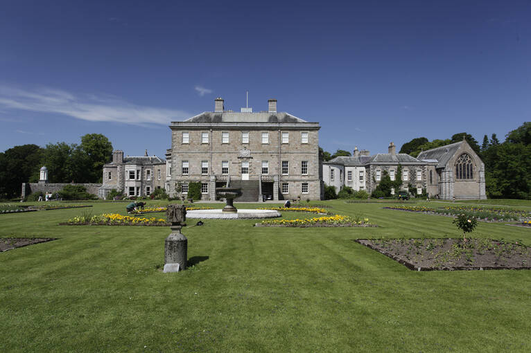 A summer view of Haddo House seen from the gardens, with a number of beds laid out and a fountain in the centre.