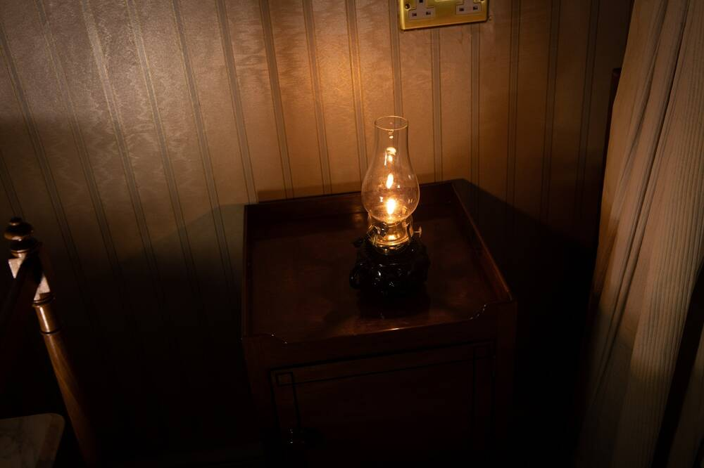 A single, lit oil lamp stands on a bedside table, casting a warm orange glow on the stripy wallpaper behind.