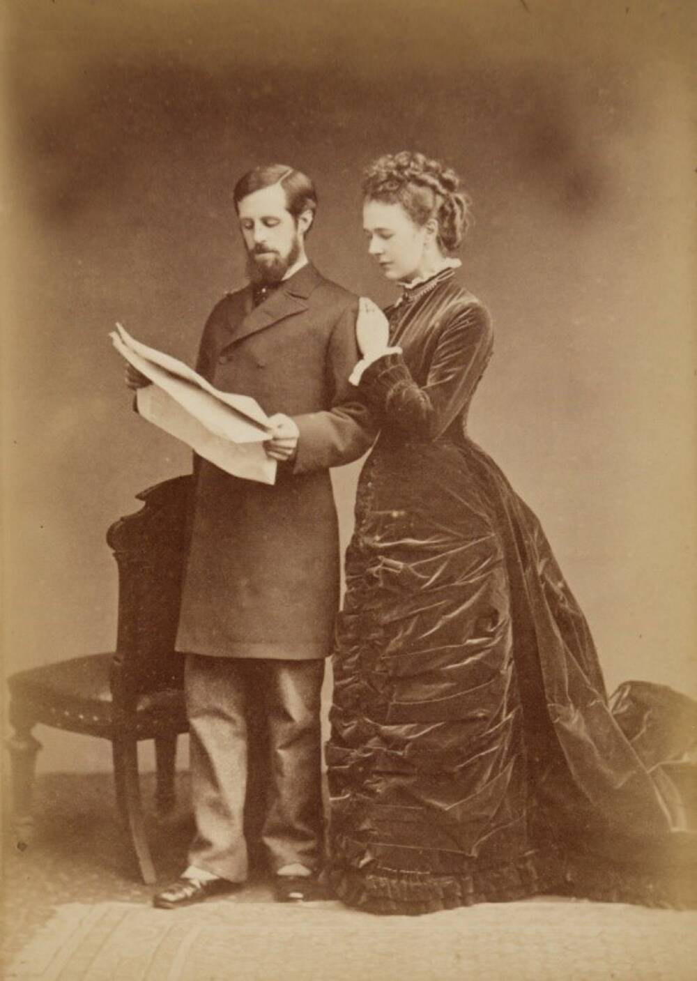 A sepia photograph of a young couple standing together in a portrait studio. The lady on the right wears a long, black dress and rests her hand on the man's shoulder. The man on the left is reading a newspaper and stands beside a chair. He has a beard and wears a smart dark coat.