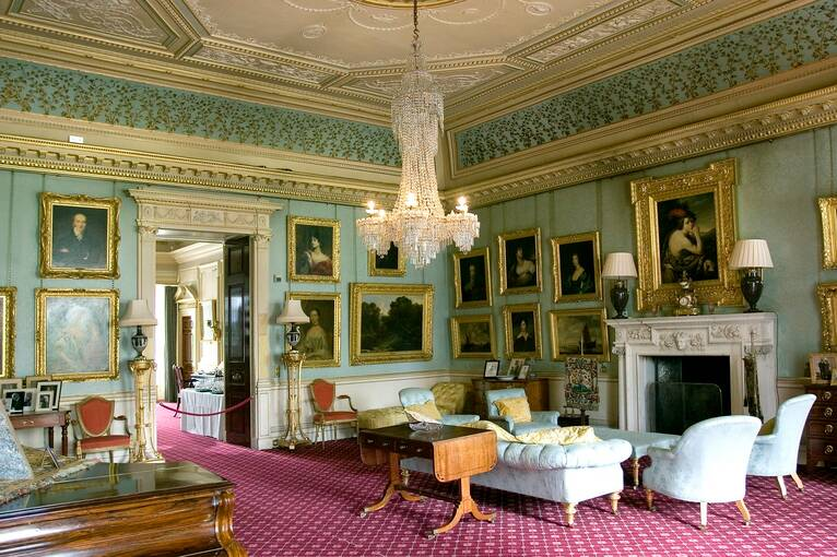 The drawing room at Haddo House, with a very large chandelier hanging from the ceiling in the centre. The walls are filled with gilt-framed portraits, and the ceiling has an ornate plasterwork design.
