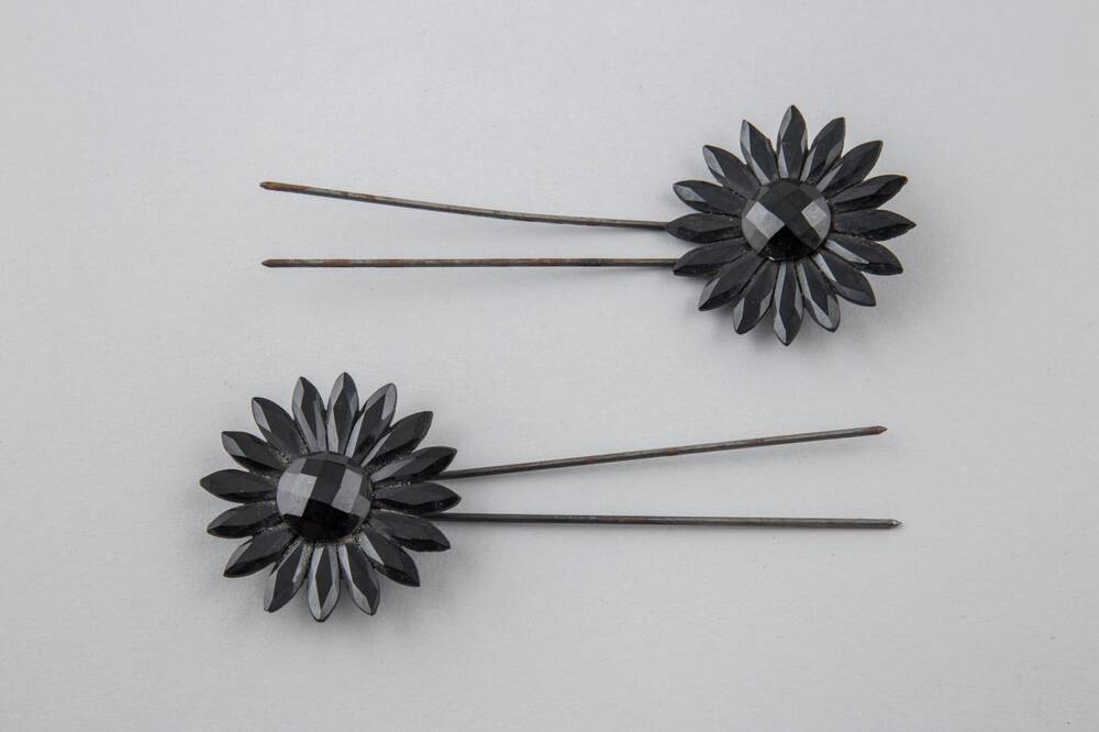 Two black hair pins with a flower design, displayed against a grey background
