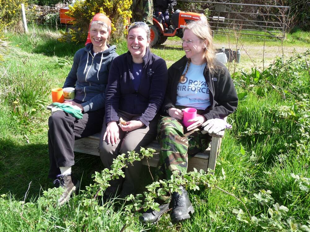 Three volunteers sit on a bench in a garden, holding mugs of tea.