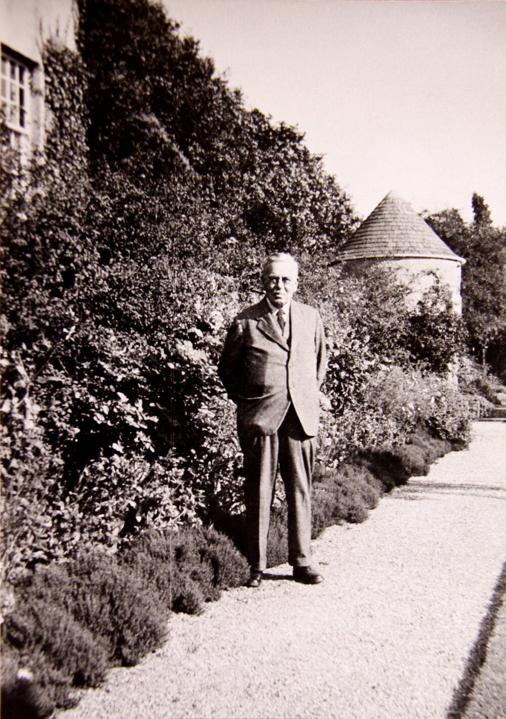A black and white photograph of an older man standing, with his hands behind his back, on a gravelled path in a garden, beside a lush border.