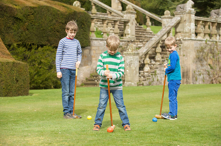 Three children playing croquet on the grass.