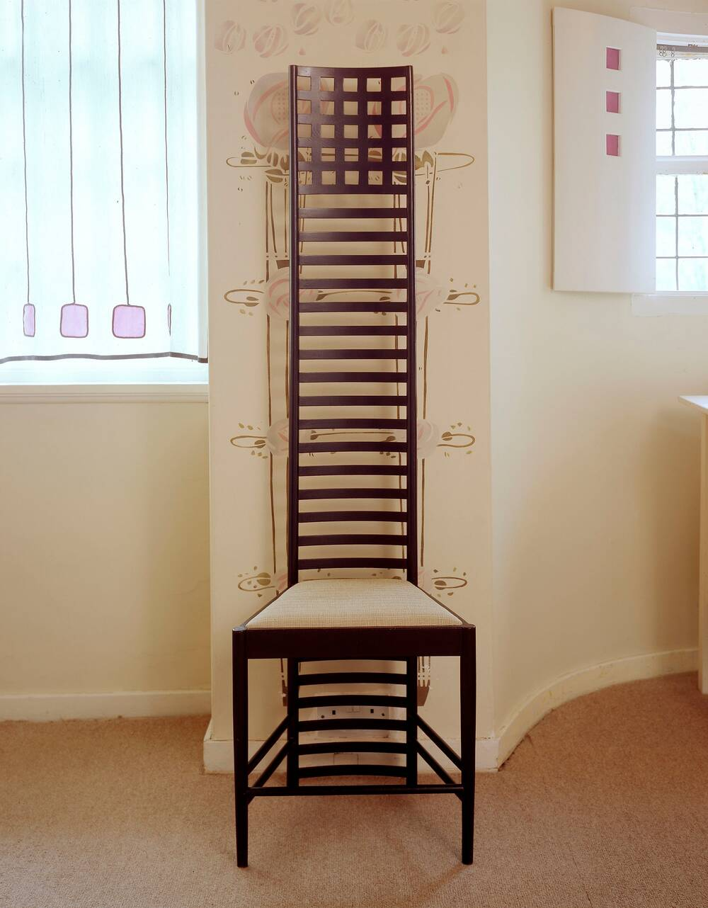 A very tall-backed  wooden chair stands against a wall that has pretty rose stencils on it, beside a window. The back of the chair resembles a ladder with many horizontal rungs. The seat is cushioned in a light fabric.