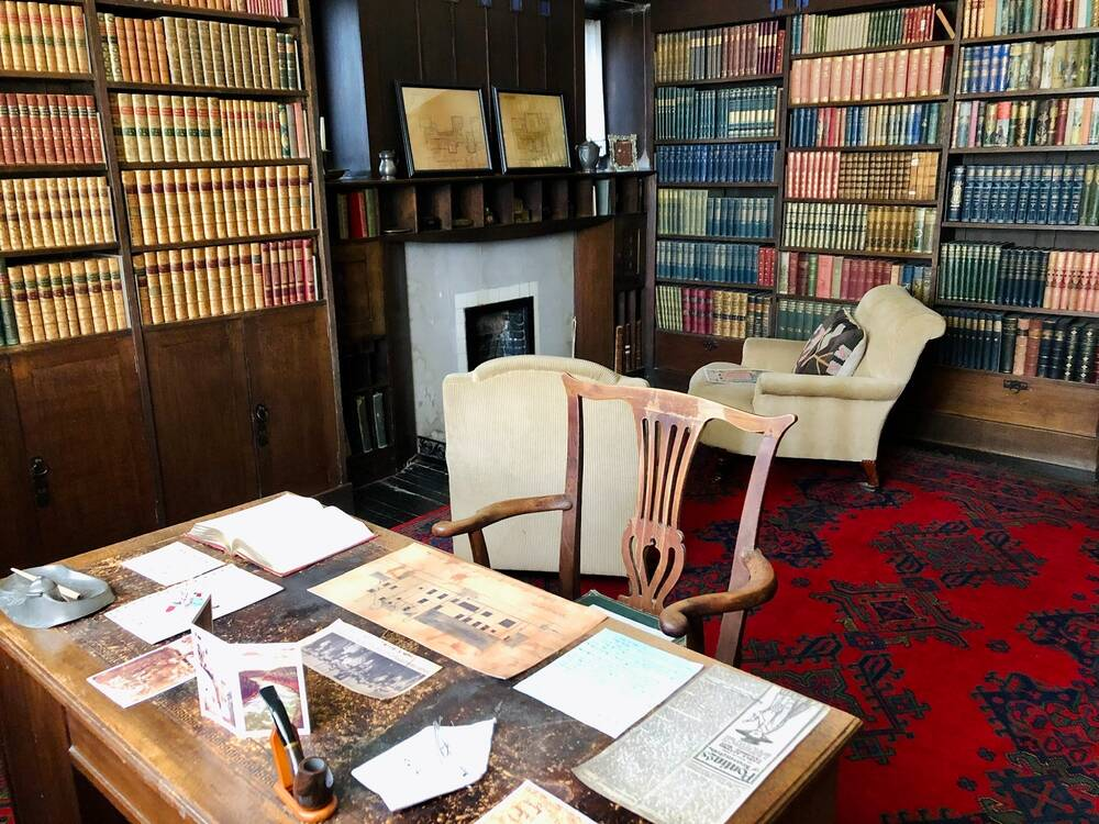 A view of an old library inside a house. A wooden desk and chair stand in the foreground, and the desk is covered in papers. In the background is a dark fireplace, with an easy chair in front. The walls are lined with dark wooden book cases, filled with books.