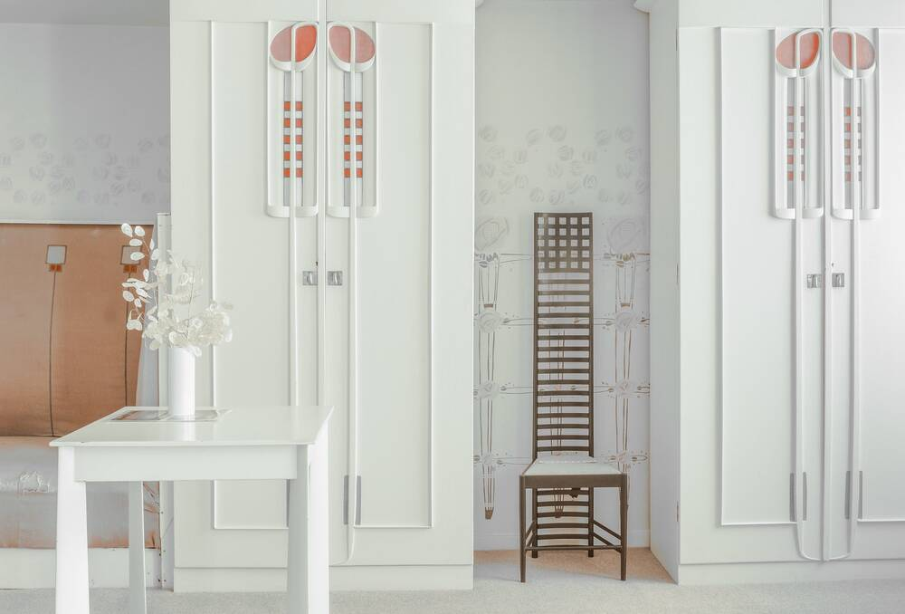 A view of part of the white bedroom at the Hill House. A ladder back chair rests in front of a wall, in between two white cupboard doors. The doors are decorated with pink Glasgow roses. A small white table stands in the foreground with a vase of white flowers on it.