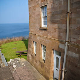 The corner wing of a large castle, with views looking out to sea. A picnic bench sits on the grassy clifftop, right in front of the castle.
