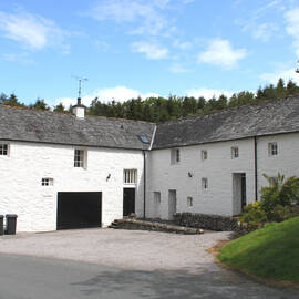 A group of white cottages surround two sides of a paved courtyard. The cottages have been converted from a mill. Large original doors and small windows can still be seen. Woodland rises on the hill behind.
