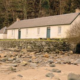A long white single-storey cottage stands just above a sandy beach, with pebbles across it. A steep hillside rises behind the cottage.
