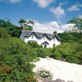 A two-storey white house stands at the top of a sandy beach, with shrubs running either side. The house is surrounded by woodland behind.