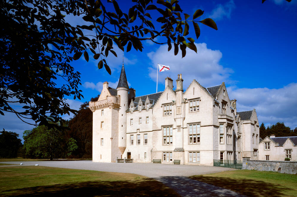 A view of the exterior of Brodie Castle, seen from the driveway on a bright sunny day.