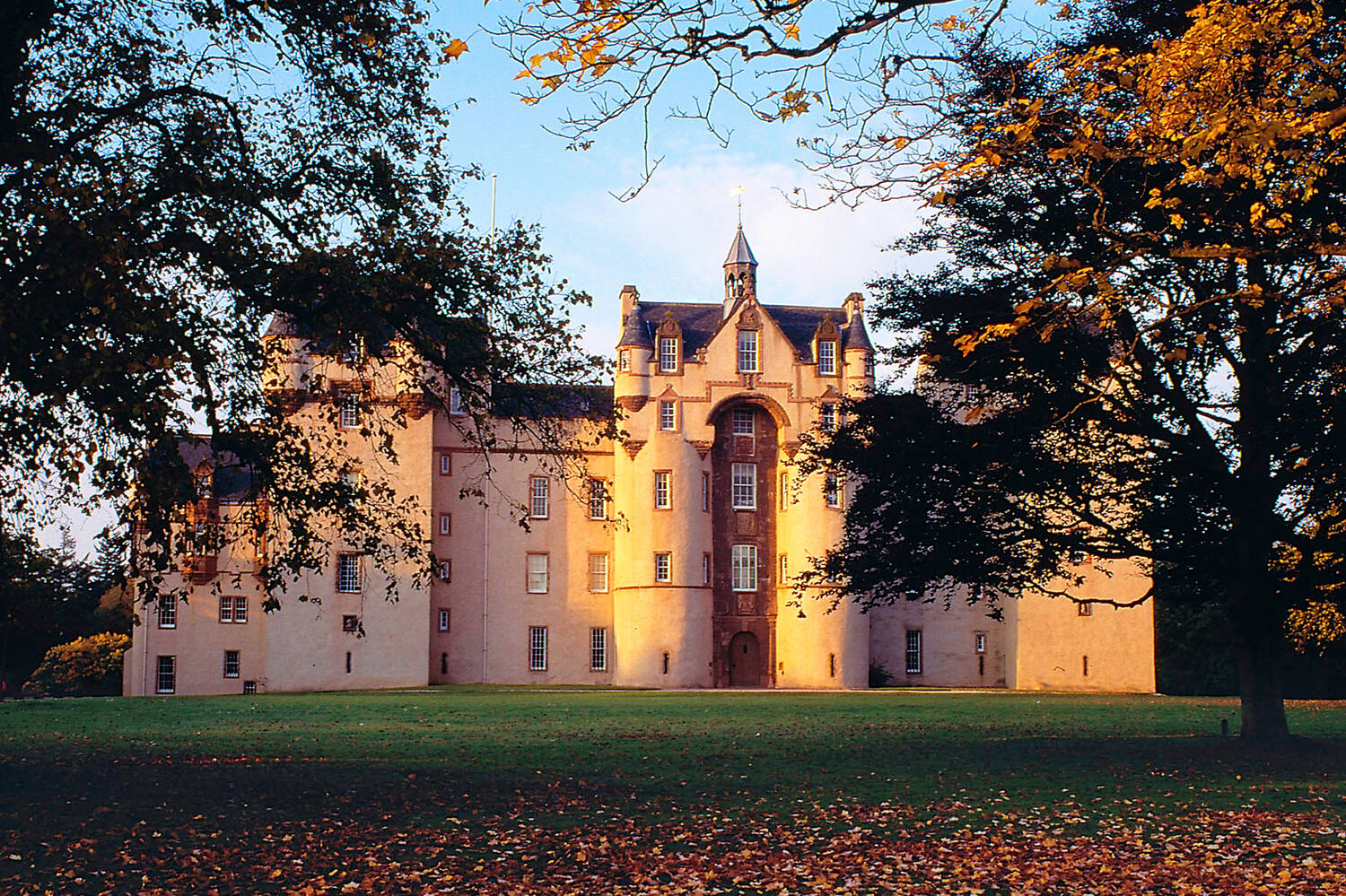A view of the exterior of Fyvie Castle, lit by the early morning sun.