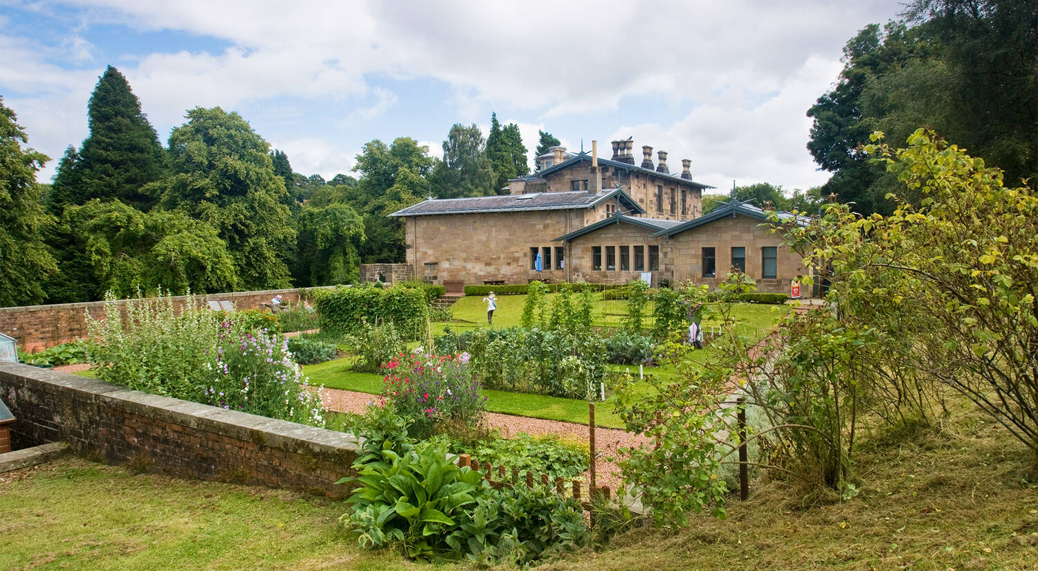 A view of the kitchen garden on a sunny day at Holmwood, with the house in the background. Several beds are laid out and surrounded by flowering borders. Currant frames can be seen at the centre. Several scarecrows stand in various beds.