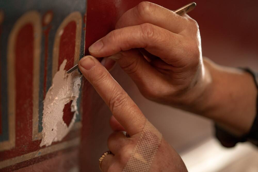 A close-up photo of hands scraping some paintwork from a stencilled decoration on the wall at Holmwood.