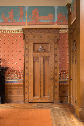 A wooden door in a grand room. The door is elaborately carved with patterns and flourishes. A frieze featuring classical characters runs around the top of the walls.