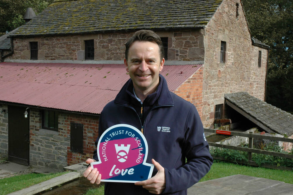 Bryan Dickson stands in front of a mill, holding an omega-shaped Trust sign.