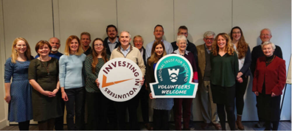 A large group of volunteers stand together holding a Trust sign and an Investing in Volunteers sign.