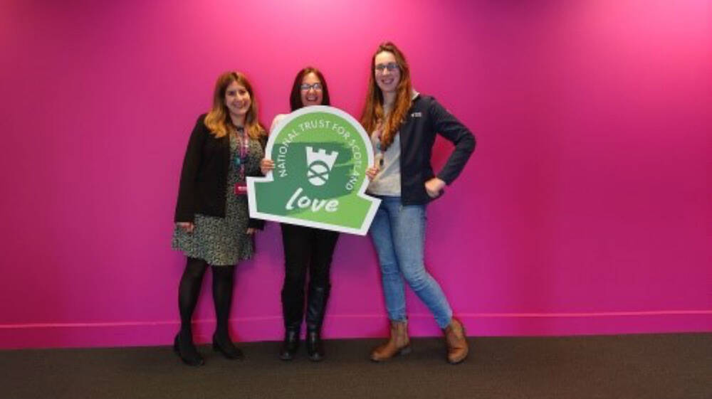 Three ladies hold a green omega-shaped sign in front of a bright pink wall.