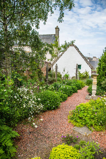 Red gravel path lies between green bushes and flower beds. Hugh Millers Cottage can be see in the background