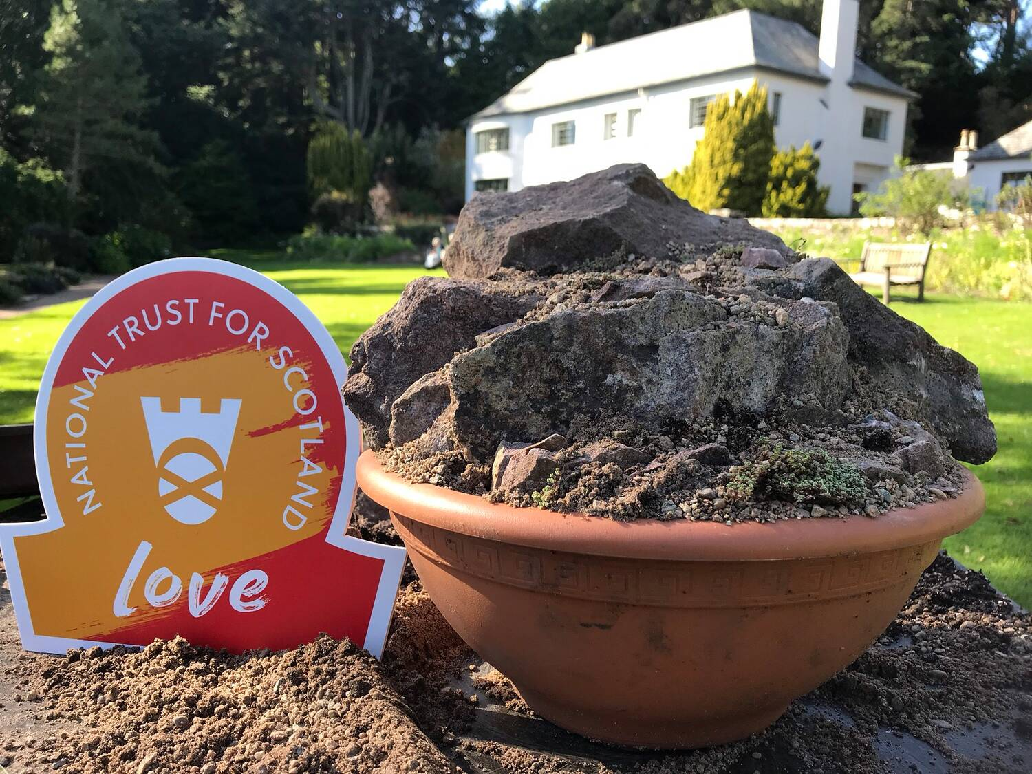 A terracotta urn filled with rocks and soil stands on the lawn in front of Inverewe House. An orange omega-shaped sign rests beside it with the text LOVE on it.
