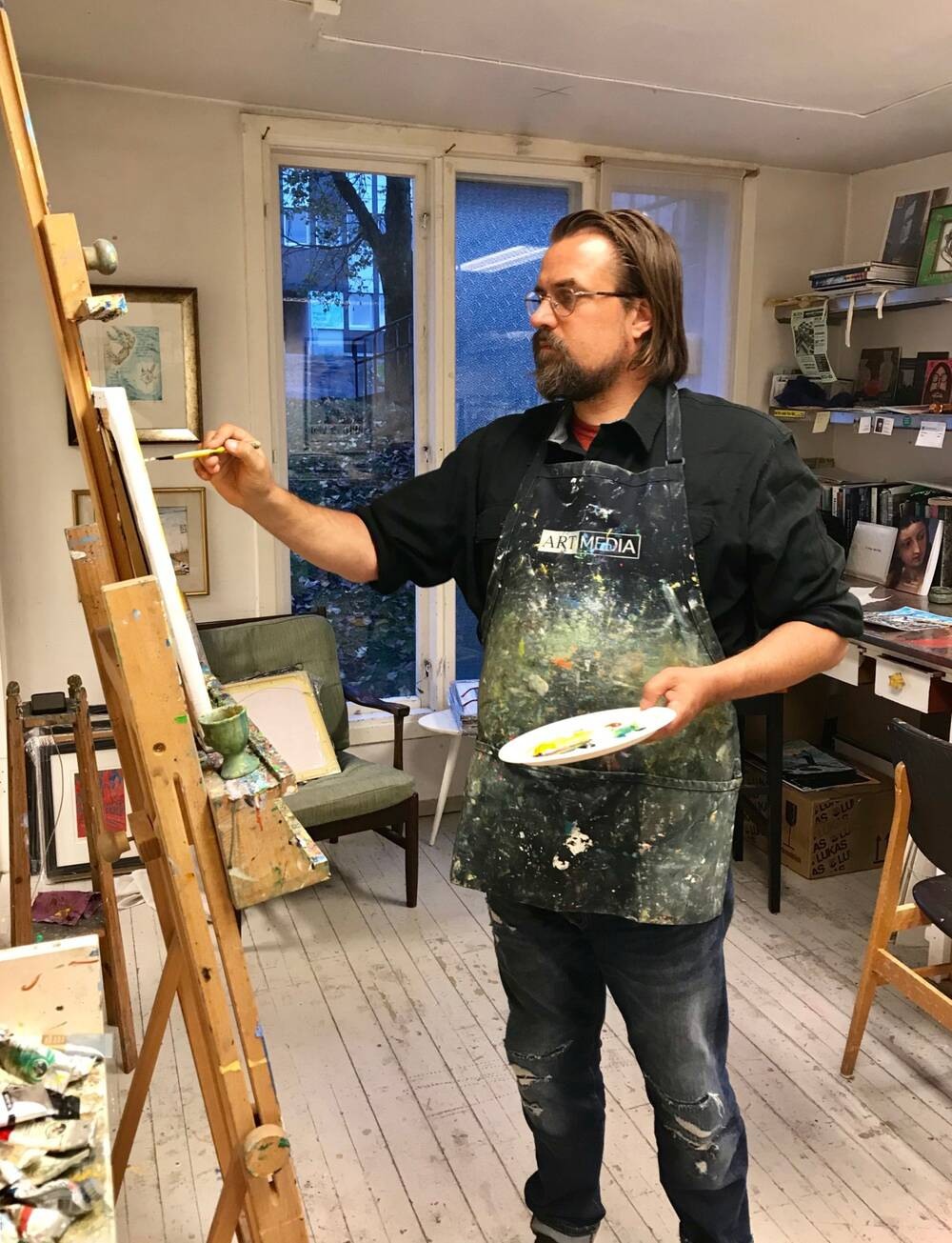 David Sandum standing at an easel, painting. He wears a paint-covered apron.