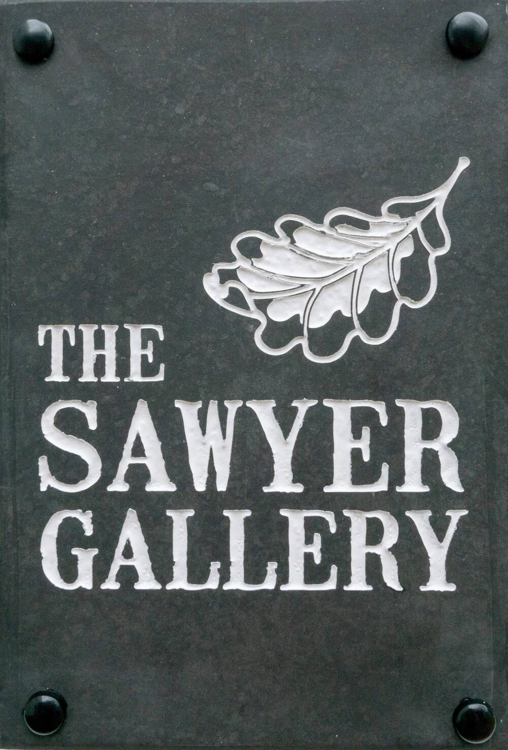 The sign for the Sawyer Gallery, featuring white text on a slate background with a leaf silhouette.