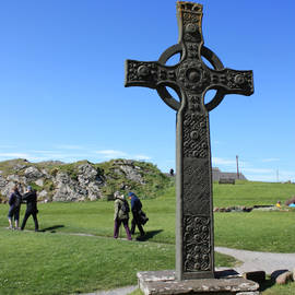 Tourists walking near St John's Cross on Iona