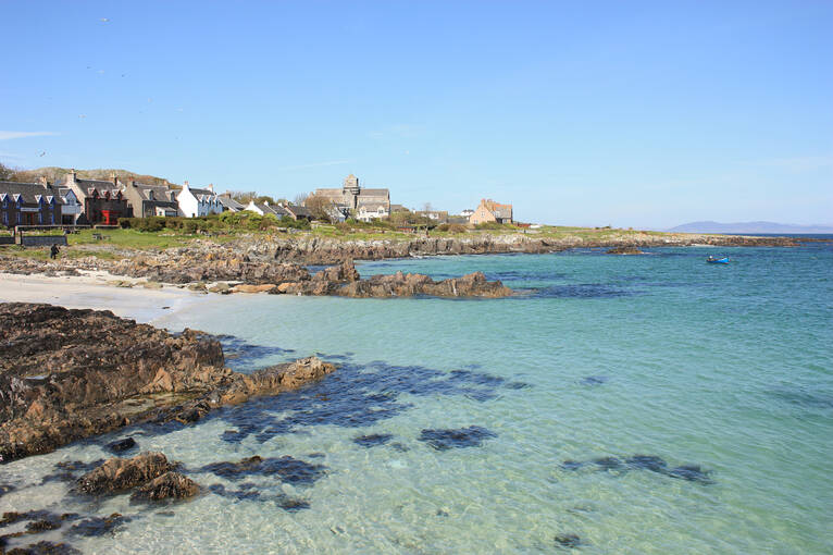 Clear water and a row of houses on the coast of Iona