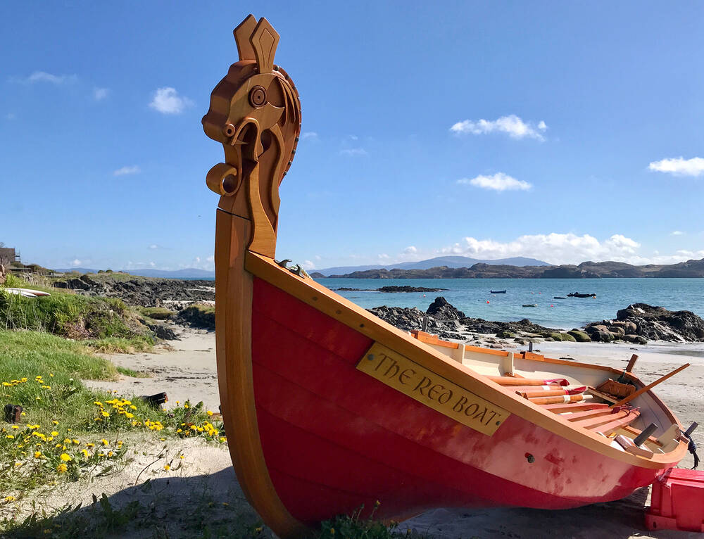 A red boat pulled up on the shore at Iona