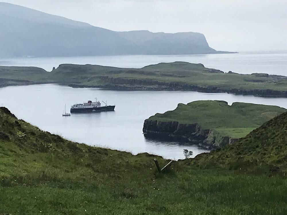 A small cruise ship is anchored in a calm bay, almost surrounded by green low-lying land except for a c