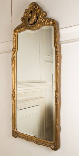 A close-up of a gold-framed mirror, reflecting white carved wooden panelling. A golden bird is carved at the top.