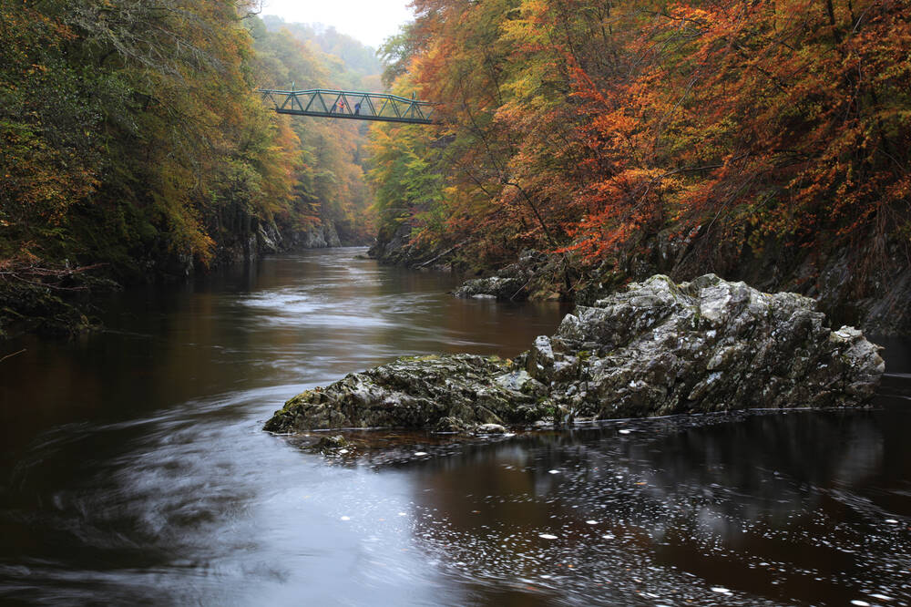Killiecrankie, with the sun shining through the autumn leaves onto the water