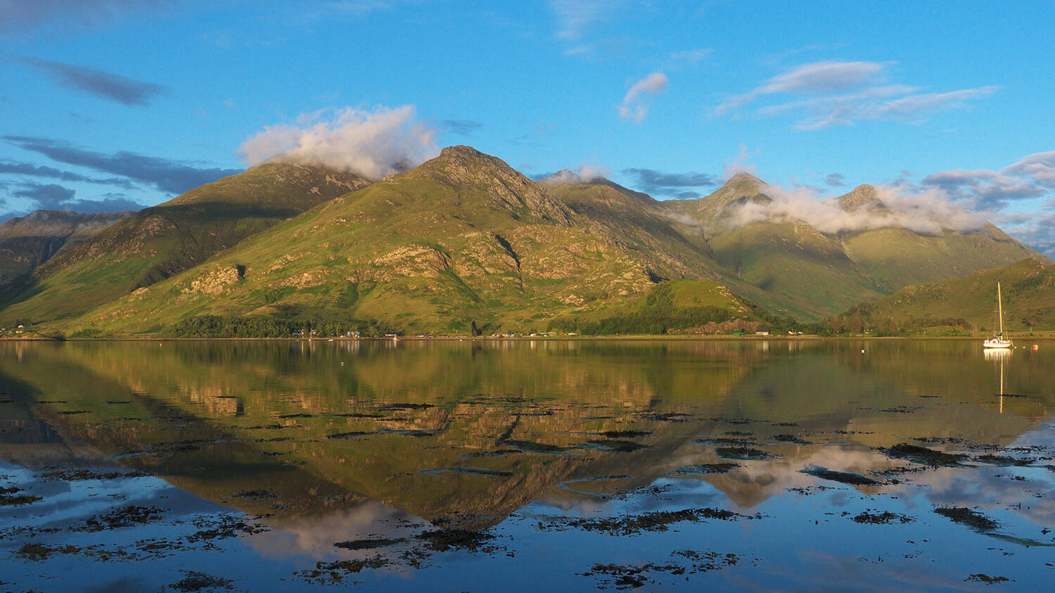 A clear reflection in Loch Duich beneath the iconic Five Sisters mountains of Kintail
