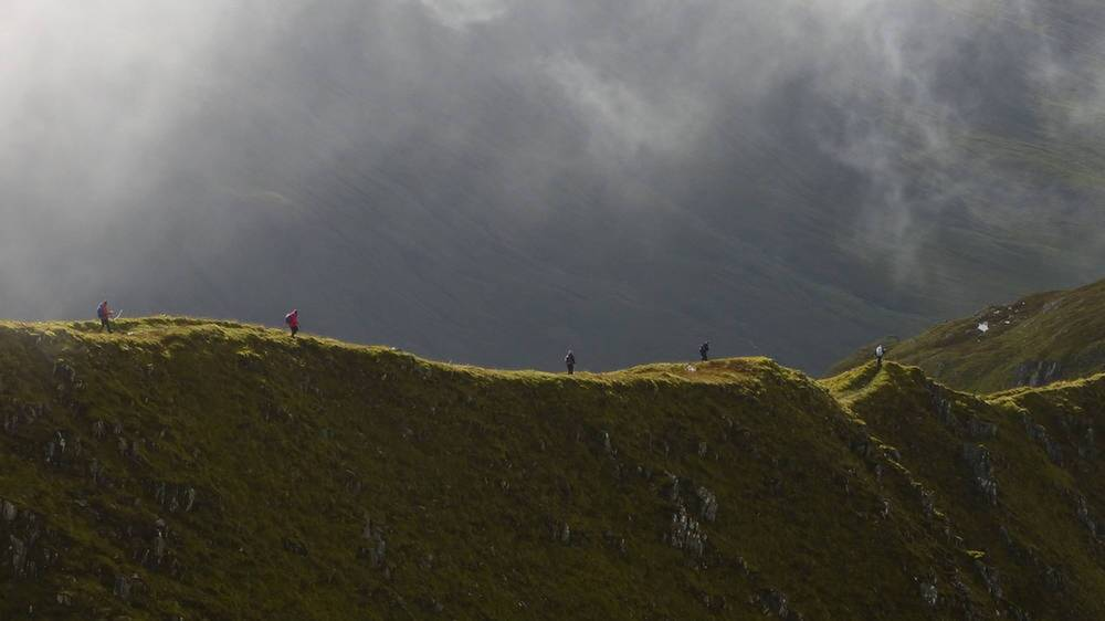 A group of people walk along a dramatic mountain ridge, under a moody sky.