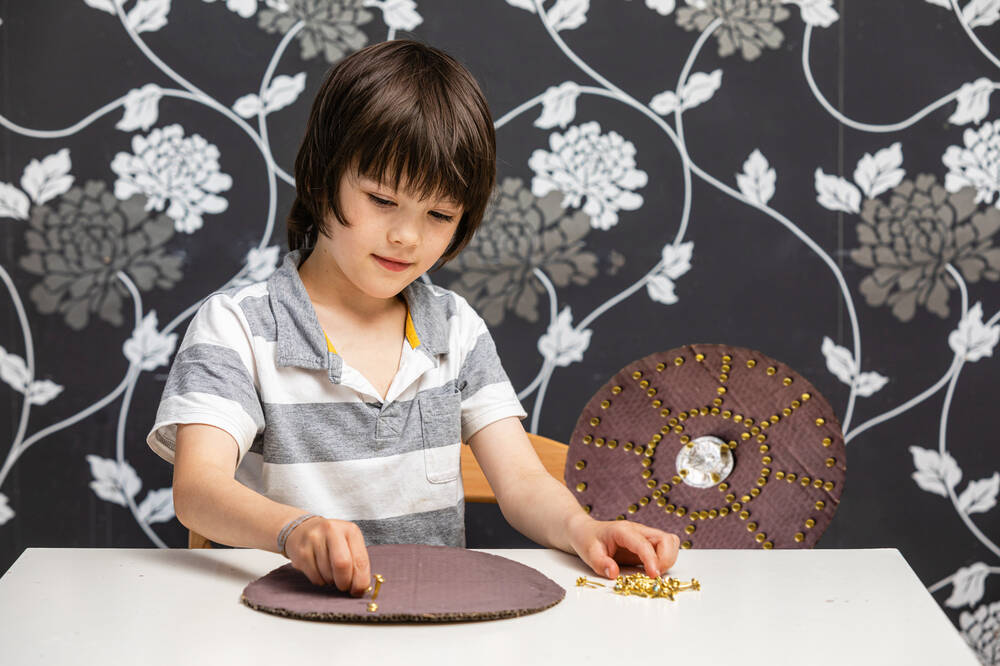 A young boy creates his own Jacobite targe from cardboard